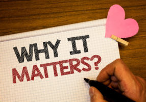 Writing note showing  Why It Matters Question. Business photo showcasing Important Reasons to do something Motivation Goal Man holding pen ideas notebook pink heart letters on wooden background